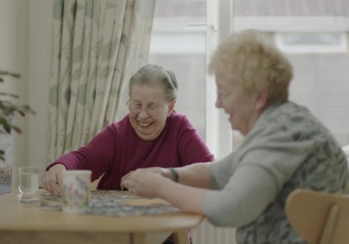 Ann and Mary sit together at a table putting together a jigsaw